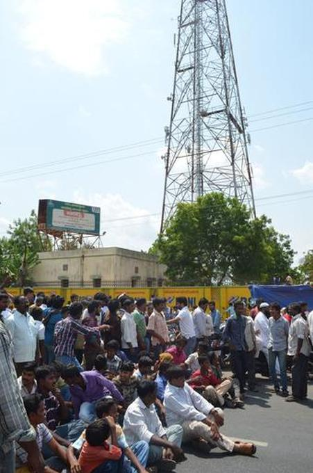 People wait for the police after Tejpal Singh refused to climb down